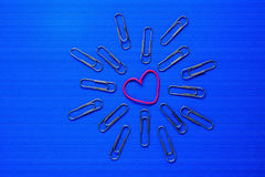 Colorful paperclips on blue background Stock Image