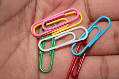 Colorful paperclips in hand. Colorful metal paper clips  in hand Stock Photos