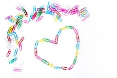 Colorful paperclips and heart on the white stock photos