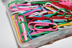 Colorful paperclips. Colorful metal paper clips on background Stock Images