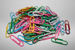 Colorful paperclips. Colorful metal paper clips on background Stock Image