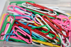 Colorful paperclips. Colorful metal paper clips on background Royalty Free Stock Images