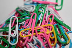Colorful paperclips. Colorful metal paper clips on background Royalty Free Stock Photos