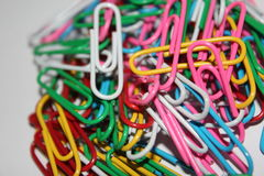 Colorful paperclips. Colorful metal paper clips on background Royalty Free Stock Photography