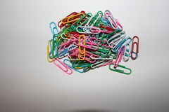 Colorful paperclips. Colorful metal paper clips on background Stock Photography