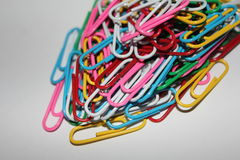 Colorful paperclips. Colorful metal paper clips on background Royalty Free Stock Photo