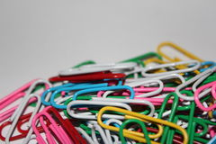 Colorful paperclips. Colorful metal paper clips on background Royalty Free Stock Image
