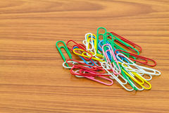 Colorful paperclips scattered on wooden floor background Stock Photos