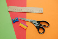 Colorful papers, scissors, pencil sharpener, ruler Royalty Free Stock Image