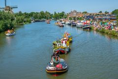Colorful parade of small, flower-decorated boats with cheerful d royalty free stock photo
