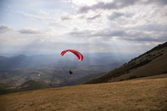 A colorful paraglider flying over Monte Cucco Umbria, Italy, with some faint sunrays. A colorful paraglider flying over Monte Cucco Umbria, Italy with some stock photography