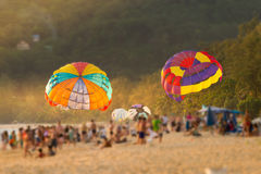 Colorful parasails showing on tropical beach,blurred crowd for background. One of the most exciting activity over the beach,parasailing  stand by in between Stock Image
