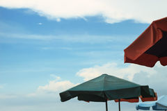 Colorful parasol umbrellas with cloudy blue sky behind Royalty Free Stock Images