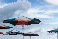 Colorful parasol umbrellas with cloudy blue sky behind Stock Images