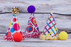 Colorful party accessories on wooden background. Colorful clowns hats and noses for kids party celebration stock photo