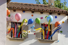 Colorful party balloons decoration on the windows of a building. Colorful helium party balloons - rainbow ballons - PortAventuras decoration near main entrance stock image