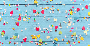 Colorful party confetti on blue wood royalty free stock photography
