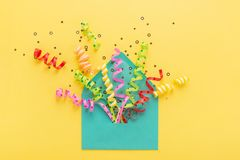 Colorful party confetti in envelope. Envelope with party confetti explosion on yellow background. Invitation card, flat lay Stock Images