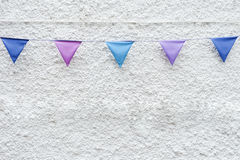 Colorful Party flags bunting hanging on white wall background. Minimal hipster style design. Stock Photography