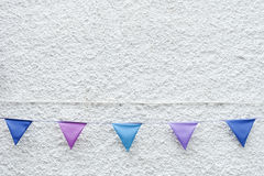 Colorful Party flags bunting hanging on white wall background. Minimal hipster style design. royalty free stock photography