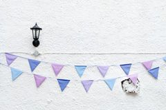 Colorful Party flags bunting hanging on white wall background with wall lamp light. Minimal hipster style design. Royalty Free Stock Photo