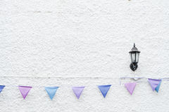 Colorful Party flags bunting hanging on white wall background with wall lamp light. Minimal hipster style design. Royalty Free Stock Image