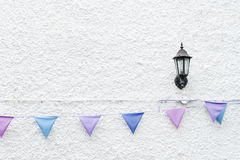 Colorful Party flags bunting hanging on white wall background with wall lamp light. Minimal hipster style design. Stock Photography