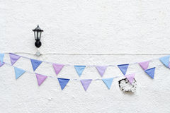 Colorful Party flags bunting hanging on white wall background with wall lamp light. Minimal hipster style design. stock photos