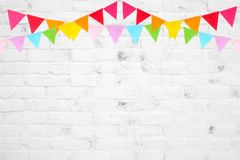 Colorful party flags hanging on white brick wall  background, bi Royalty Free Stock Image