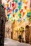 Colorful Party flags wave in a little alley Stock Photography