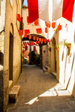 Colorful Party flags wave in a little alley Stock Photos