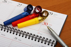 Colorful party whistles and a pen on the agenda. Colorful party whistles and a penlying on the office agenda Royalty Free Stock Photos