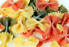 Colorful pasta bows. Some yellow, green and red pasta bows against a white background royalty free stock photography