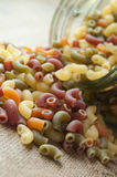 Colorful pasta fall from glass container on wooden background Stock Images