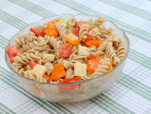 Colorful Pasta Salad. Made with spiral multigrain pasta, fresh vegetables, cheddar cheese and dijon dressing. served in a glass dish on a green and white royalty free stock photography