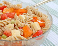 Colorful Pasta Salad. Made with spiral multigrain pasta, fresh vegetables, cheddar cheese and dijon dressing. served in a glass dish on a green and white stock image