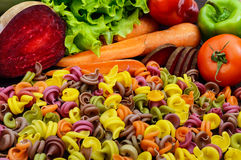 Colorful pasta on a table with fresh vegetables beets, greens, carrots, tomatoes, peppers. Royalty Free Stock Photography