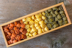 Colorful pasta in wooden box. Colorful pasta, on wood background Royalty Free Stock Images