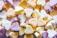 Colorful pastel candy hearts background. White, orange, purple colored sweet candy hearts, abstract pastel background Royalty Free Stock Photo