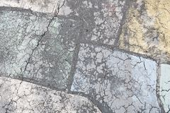 Colorful pastel cracks in painted pavement. Cracks and pastel color create abstract patterns on worn pavement surface stock photography
