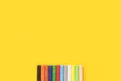 Colorful pastel crayon. Twelve colorful pastel crayon lay on yellow background Royalty Free Stock Photography