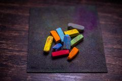 Colorful pastel crayons for drawing on old wooden surface. stock photos