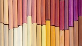 Colorful pastel crayons in warm colors in two rows as background stock images