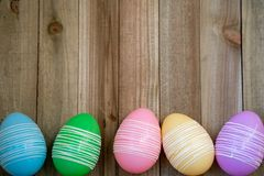 Colorful pastel easter eggs, bottom aligned, on a wood background. Flatlay flat lay background for spring stock photography