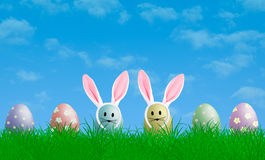 Colorful pastel easter eggs with bunny ears in grass with blue sky background, copy space. Colorful bright pastel easter eggs with bunny ears in grass with blue Stock Image