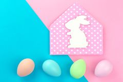 Colorful pastel easter eggs on pink and blue with bunny envelope stock photography