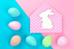 Colorful pastel easter eggs on pink and blue with bunny envelope stock image