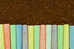 Colorful pastel sidewalk chalk on dark asphalt background. Royalty Free Stock Photography