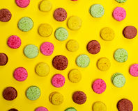 Colorful pastry macarons on a yellow background Stock Photos