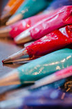 Colorful pastry piping bags and silver tips. Royalty Free Stock Photos
